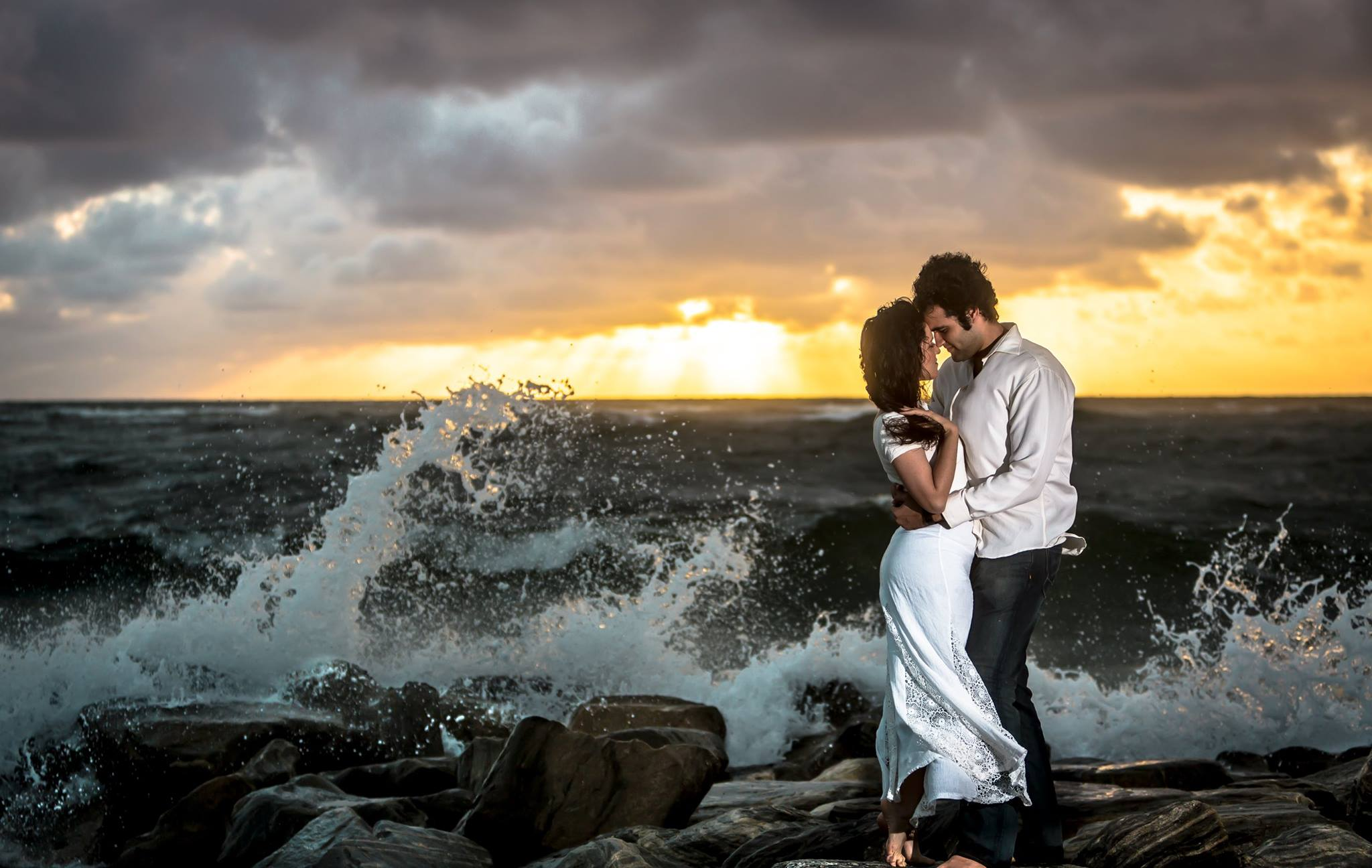 Man and woman in an embrace on the rocks with the waves crashing around them during an engagement photography session in Palm Beach, Florida