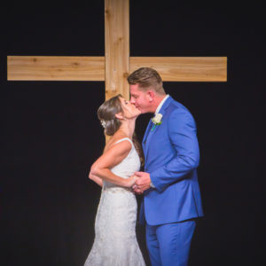 Bride and groom first kiss after being pronounced man and wife during their wedding at the Christ Fellowship Church in Palm Beach Gardens, Florida. Photography by Palm Beach Florida's best Wedding Photography Studio Couture Bridal Photography Alfredo Valentine